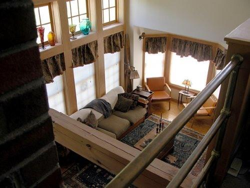 View of the high ceiling Living Room w/ woodstove & center chimney from loft