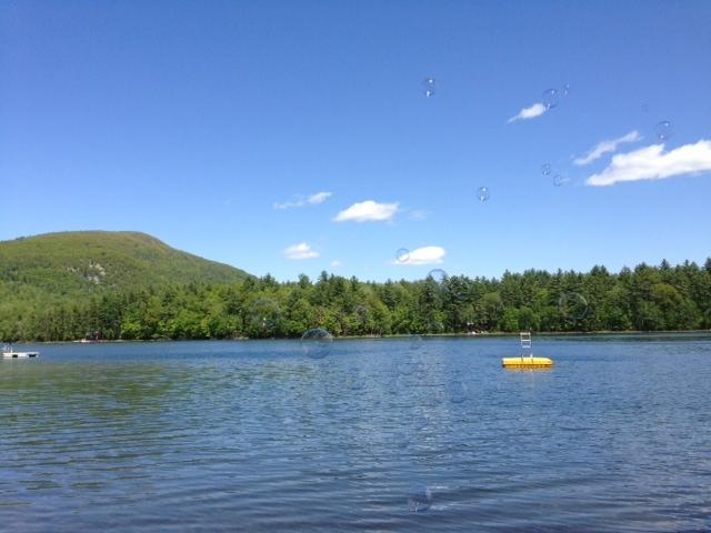 View from beach of private swim dock and Pleasant Mountain