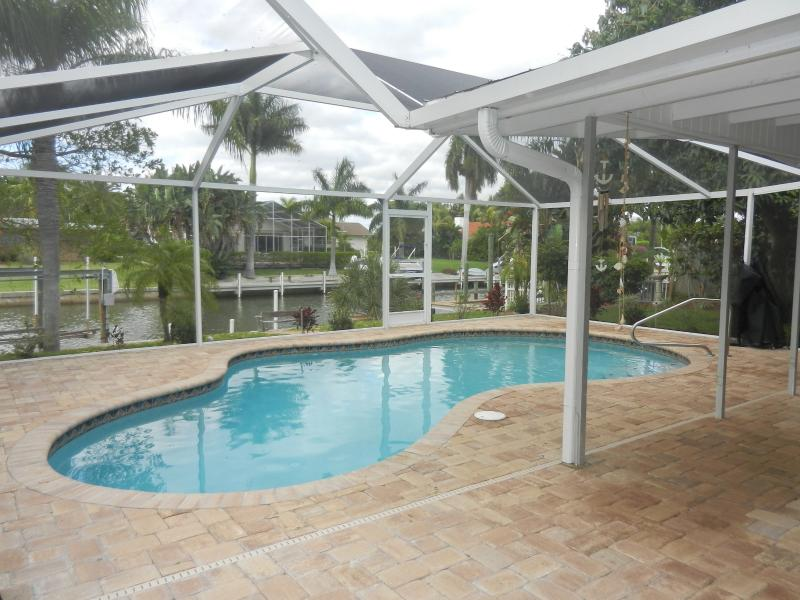View of the canal. Tile patio. Saltwater pool and lanai.  Beautiful landscaping.