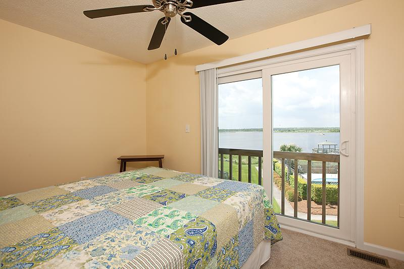 Upstairs bedroom with queen size bed, tv, and view of the pool, sound and ICWW.
