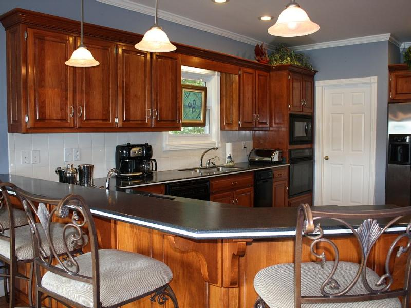 Bar seating for four looks into the gourmet kitchen.