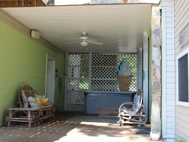 Lower level covered patio has a shower and hot tub to relax in.