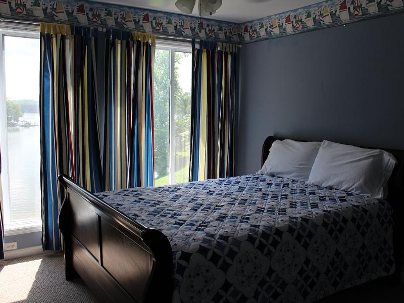 Upstairs bedroom looks over the lake with a queen size bed.