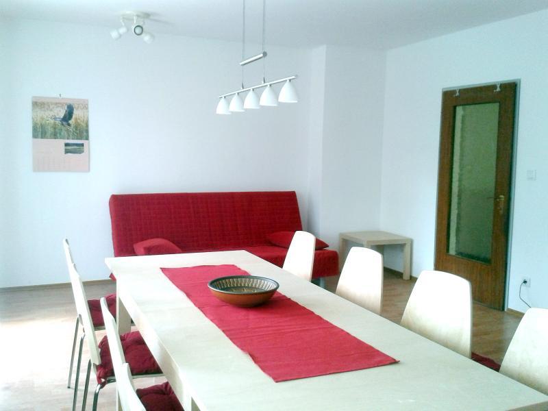 Grande table à manger dans le salon. À l'arrière-plan la deuxième sofa.