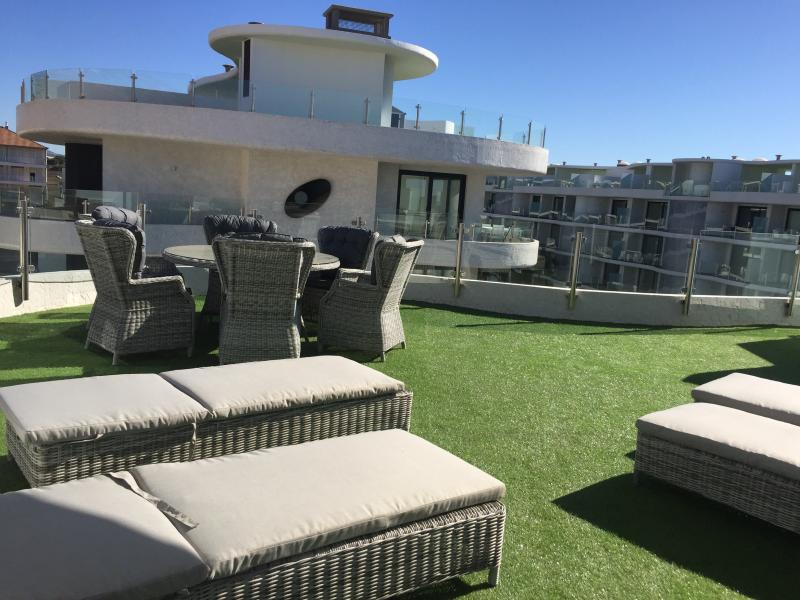 Private solarium terrace with sun beds, dining tables and lounge seating.