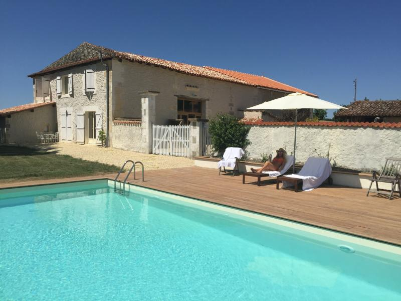 10m x 5m south facing salt-water swimming pool, with a deep sun deck and wooden sunbeds