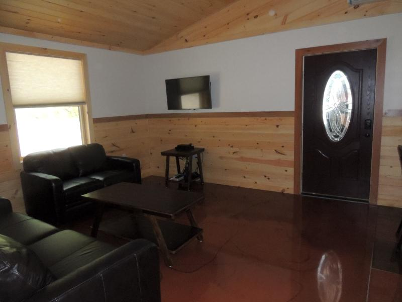 Comfy cozy living room with leather couches, Satellite TV, DVD player & movies, games & books.