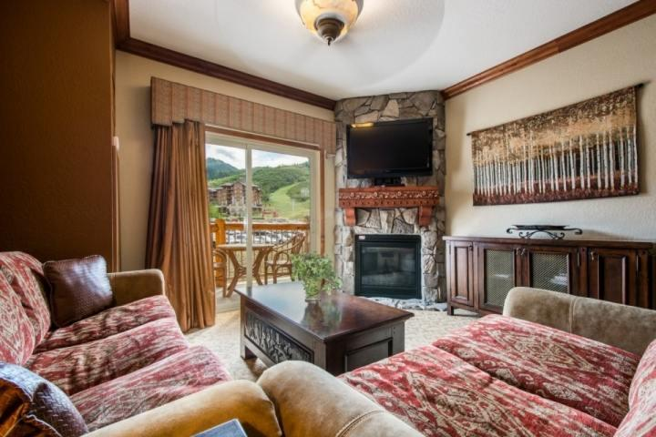 Living room / family room with comfortable furnishings, gas fireplace, flatscreen HDTV and pull out queen size sofa bed.