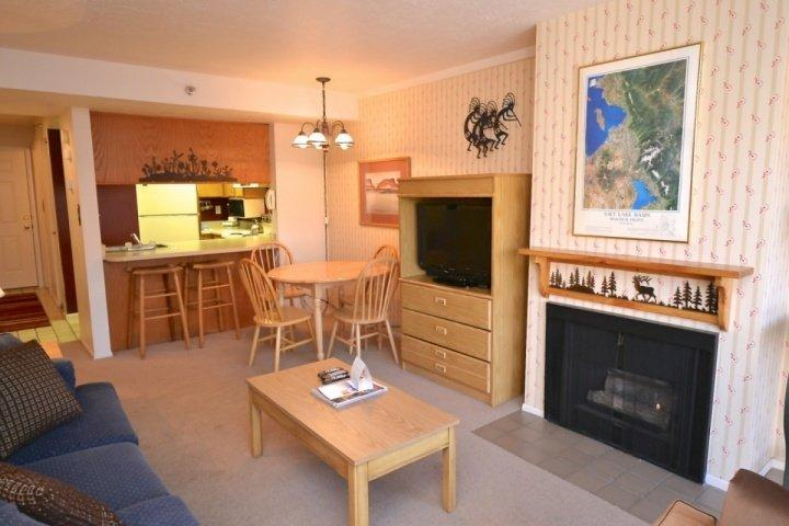 Welcome to our Prospector Square Home! The living room is equipped with a gas fireplace, flat-screen TV and plush sofa.