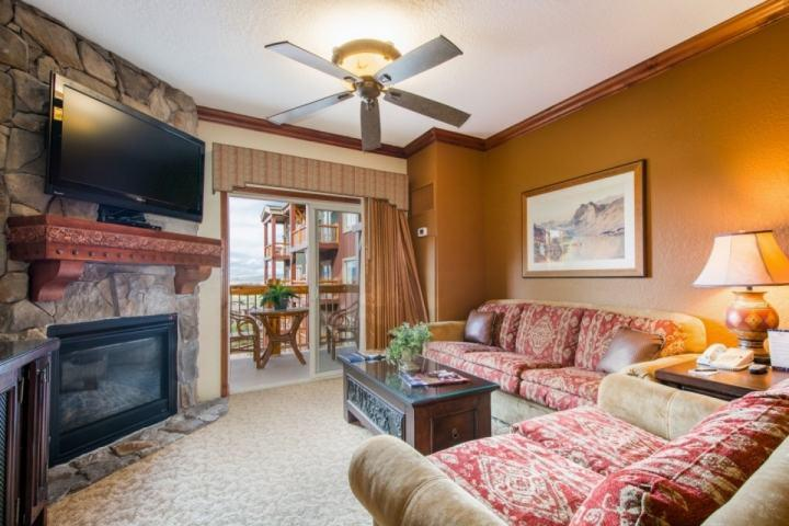 "The living room is equipped with a plush couch, love seat, 50"" HDTV, enhanced cable, DVD player, Wi-Fi and beautiful stone fireplace."