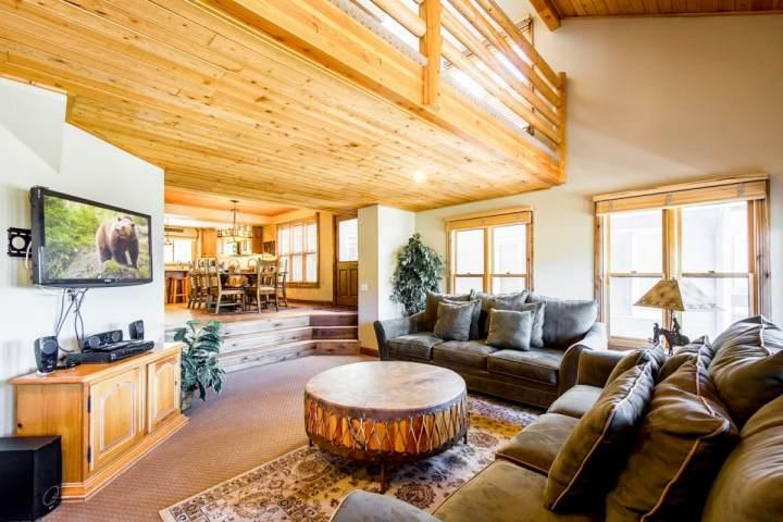 The living room is equipped two (2) plush couches that surround wood-burning fireplace with floor to ceiling stonework and the entertainment center.