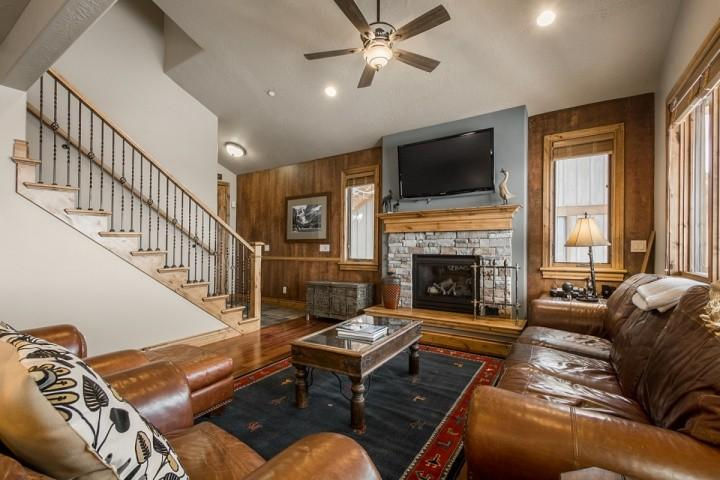 The large formal living room features beautiful leather furniture, hardwood floors, vaulted cathedral ceilings, 50' HDTV and gas fireplace with stone