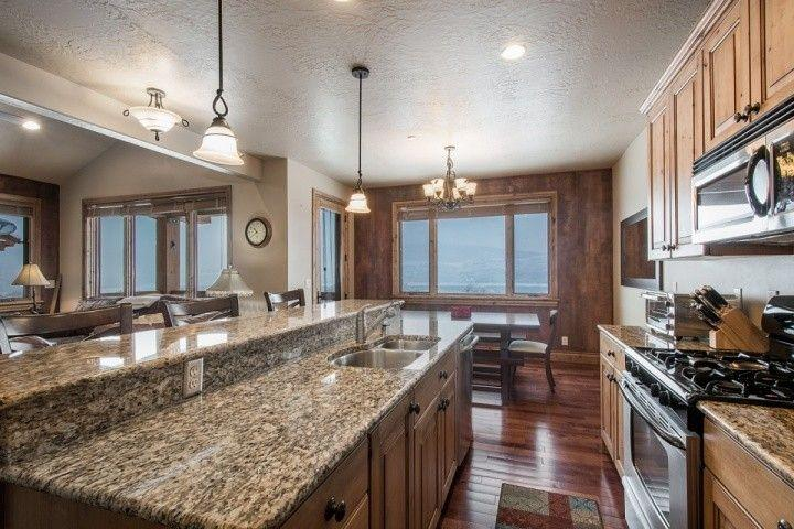 The kitchen also features a custom kitchen island, which further extends the prep and entertainment space and also has a breakfast bar with bar stool
