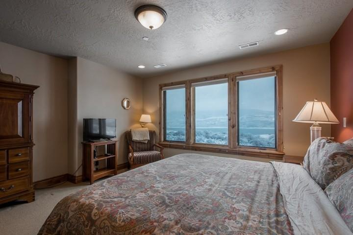 The first bedroom (1) also features a large armoire for storage, 32' HDTV, lounge chair and two nightstands with lamps.