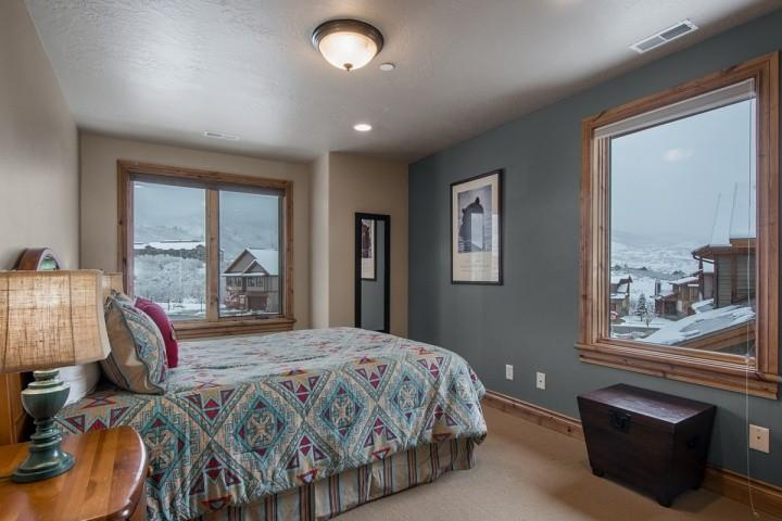 The second bedroom (2) is a corner room and features a queen size bed with hardwood bed frame and dresser for storage.