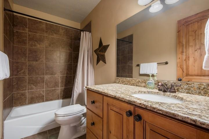 The second bathroom (2) features an extra long granite counter top with vanity, bronze finishes, bathtub and shower.