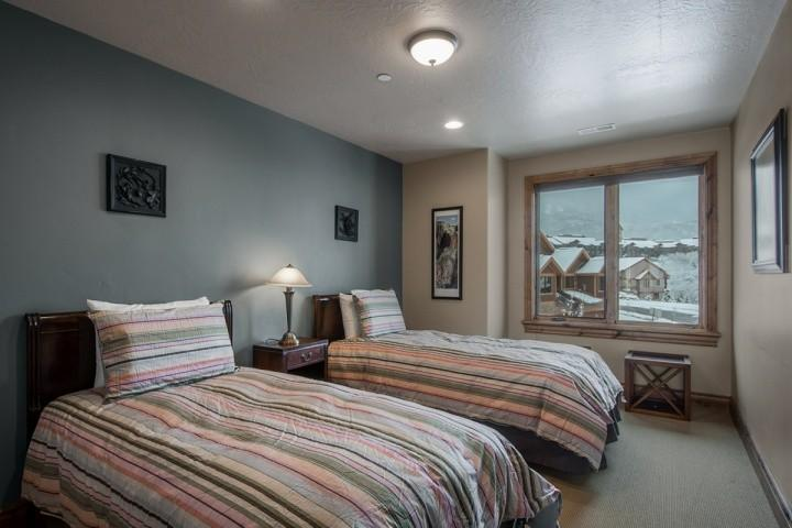 The fourth bedroom (4) features two (2) twin beds with hardwood bed frames, comfortable linens and bedding and nightstand with lamp.