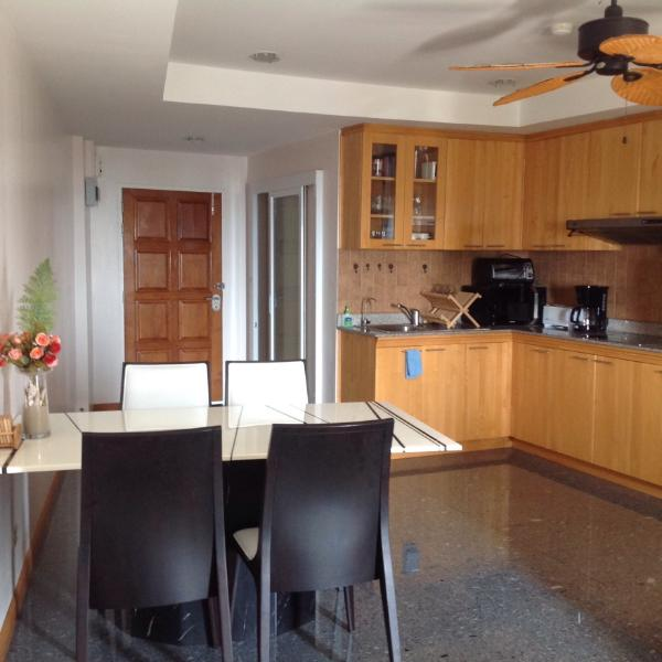 Front entrance to condo showing fully equipped kitchen and lovely stone dinning room table.