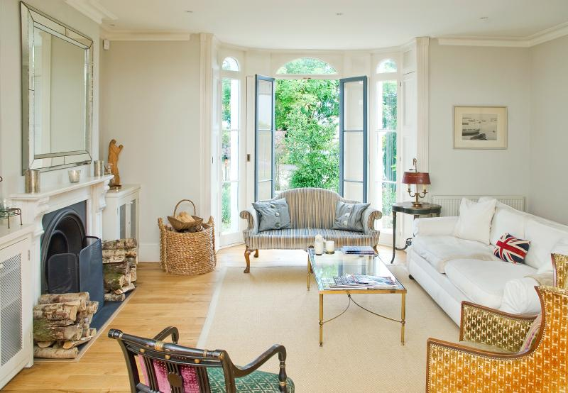 Drawing Room with open log fireplace, french windows with original shutters leading to front garden.