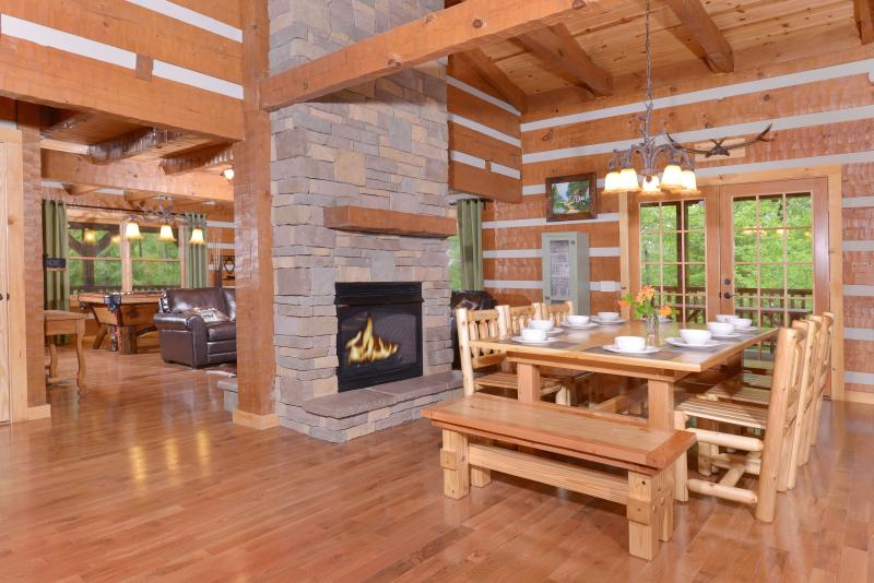 Open concept dining room with fireplace and farmhouse style table that seats 10