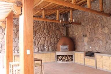 Area social con horno de barro, parrilla y comedor con vista del Valle