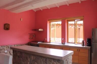 Cocina completa integrada al comedor, en color rosado colonial