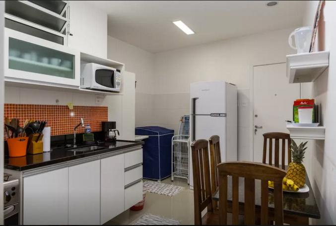 The kitchen and service area with clothes washer and utility basin.