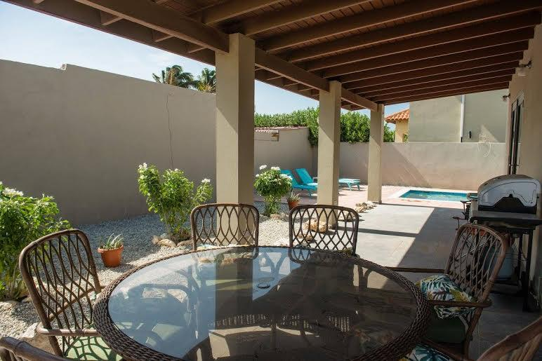 Spacious covered porch with BBQ and outdoor dining area adjacent to pool and lounge area