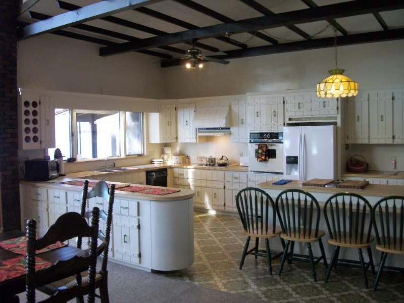 Fully equipped kitchen includes plates, drink containers, flatware, cookware, utensils, servingware.
