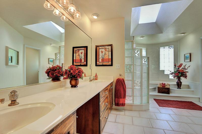 Bright and airy West Coast Villa I Master Bathroom with glass block windows, skylight, double sinks