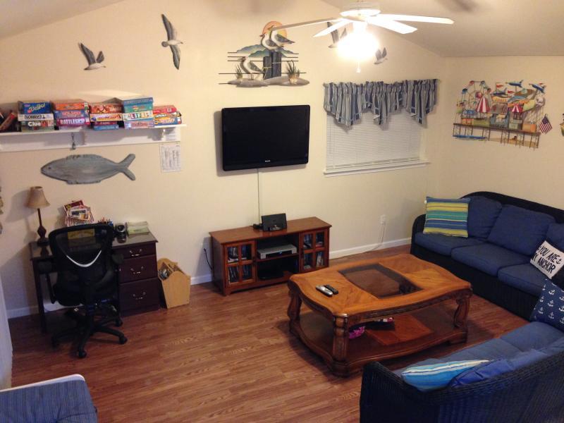 Familiekamer met chocolade harde houten vloeren en rieten sofa 's