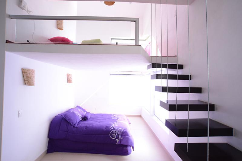 Habitación rosa. Arriba la cama en el tapanco... abajo otra cama doble