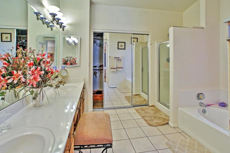 The master bathroom features a walk-in shower and separate tub.