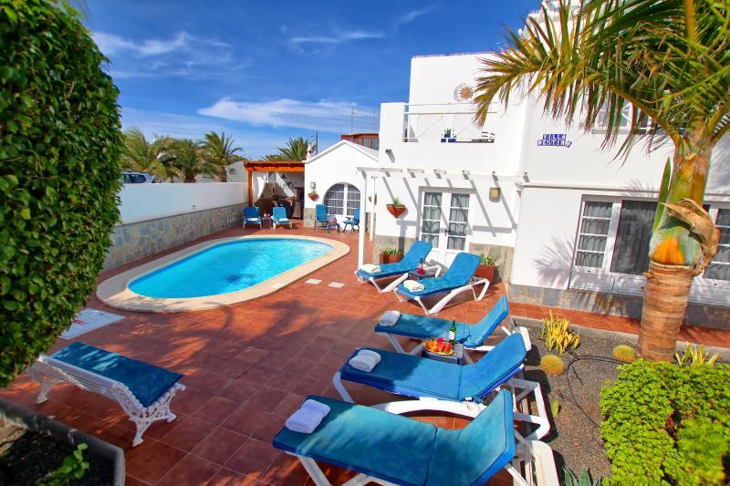 Terraza frontal de palmeras con piscina climatizada de agua salada y tumbonas
