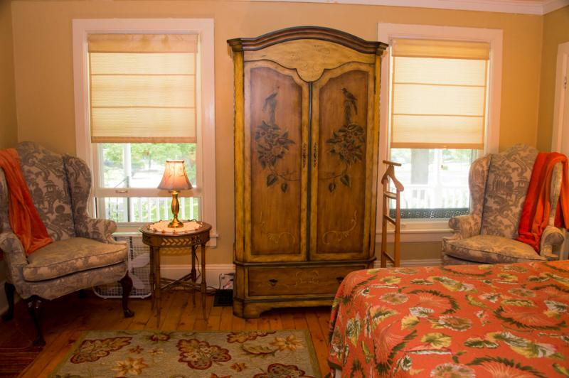 Master bedroom with queen bed off living room adjacent to paneled bedroom
