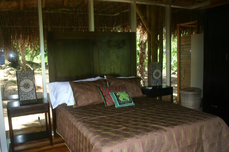 Queen bed in the other pavilion, has a chair,2 night tables & a large wardrobe