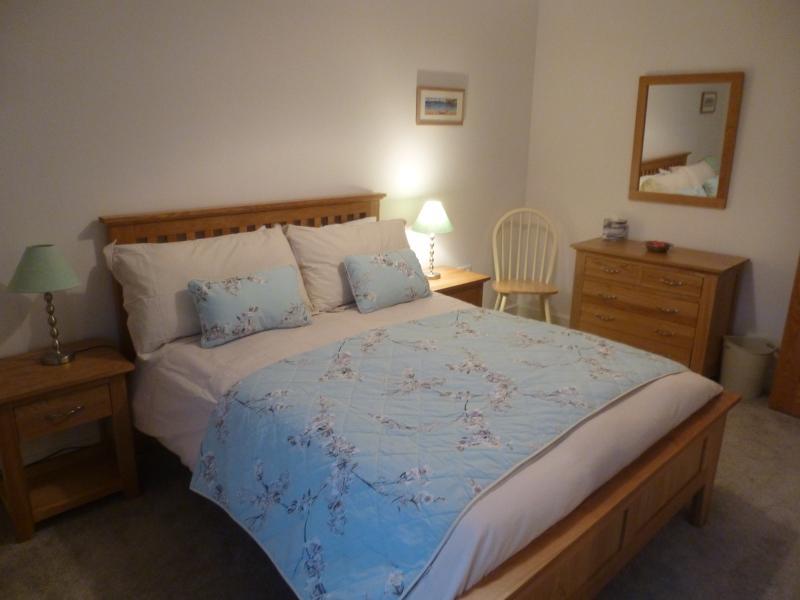 Spacious 2nd bedroom bed with large mirror door wardrobes.