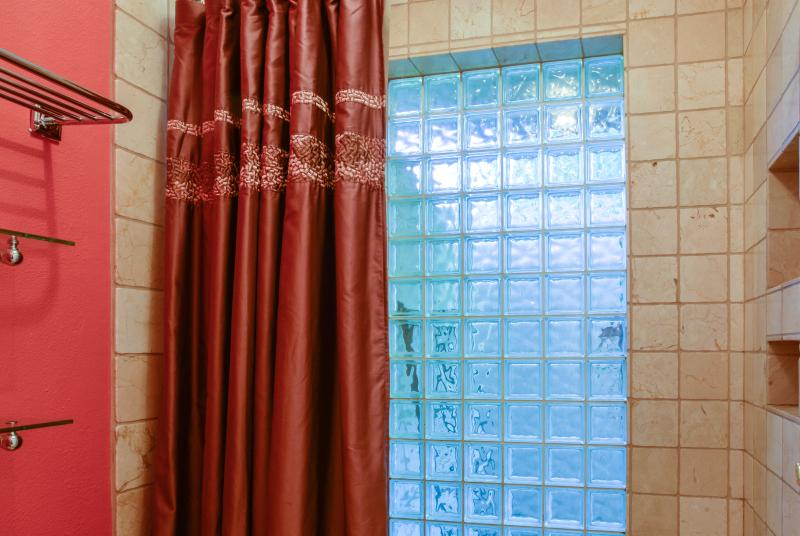 Master shower with glass block and crema marfil tile on walls and floor