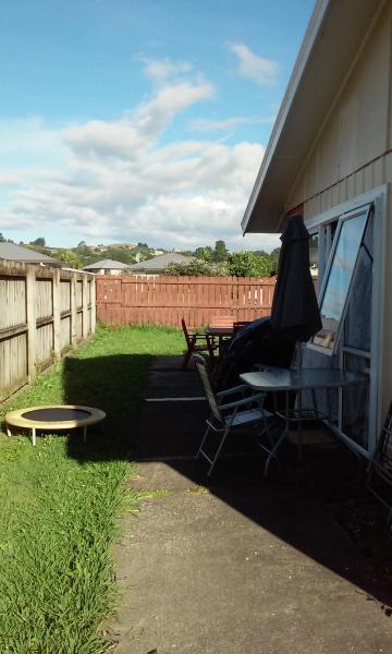 Lado da casa, porta deslizante, mesa e cadeiras para relaxar ao ar livre