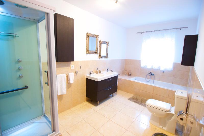 Baño principal con lavabo doble, cabina de hidromasaje con radio y bañera