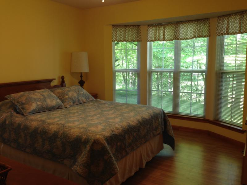 Guest room with queen bed and bay window for beautiful view.