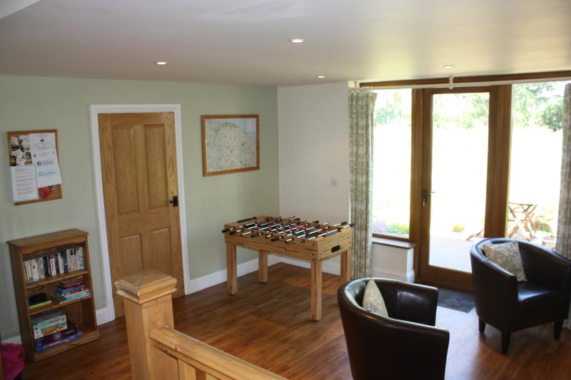 Family TV room with football table leads to the breakfast patio