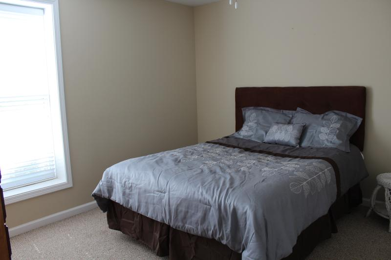 Lower level bedroom has a view of the lake and a queen bed.