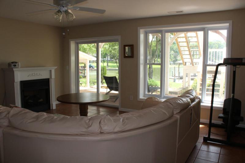 Lower level living room has a fireplace and walks out to covered patio and lake