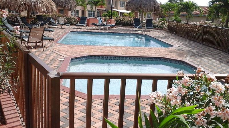 Gated ground floor condo with a pool view and a private tiled back patio