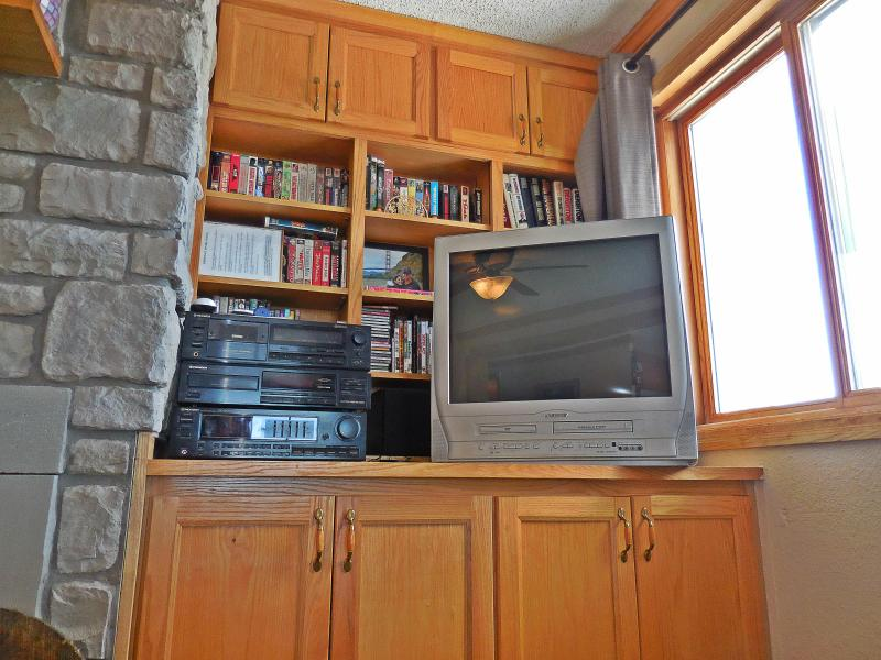 Oak entertainment center with TV, stereo, and books/movies
