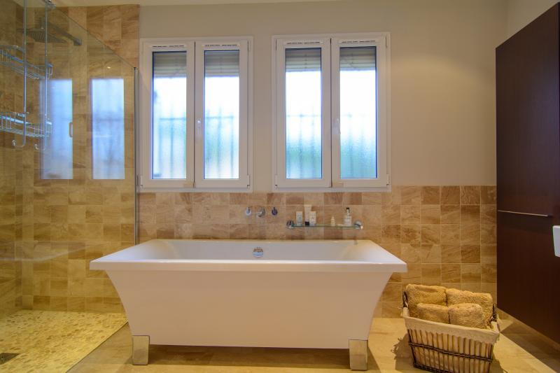 En suite bathroom with bathtub and shower cabin
