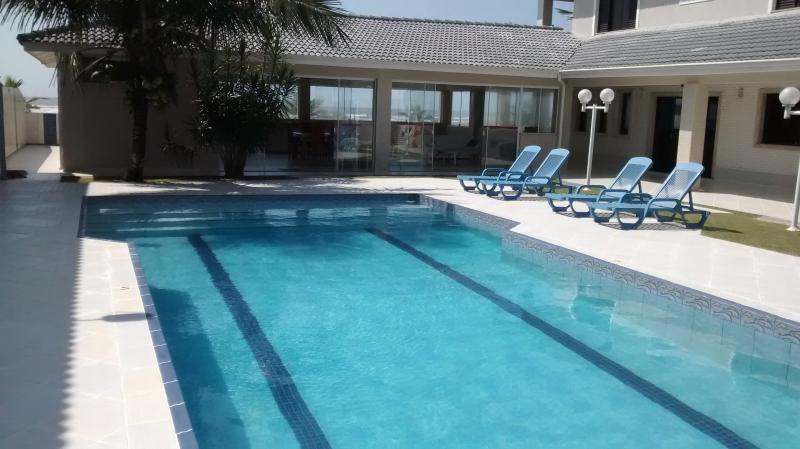 Vista da piscina com o salão e o mar ao fundo