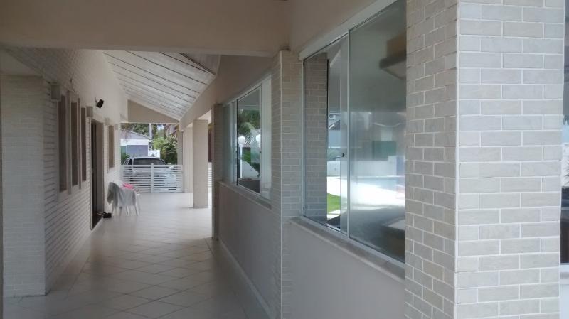 Visão parcial da varanda com lateral do salão do lado direito e da casa do lado esquerdo.