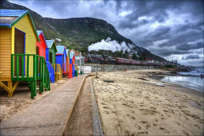 Colourful St James beach bathing boxes with the coastal railway line close by,